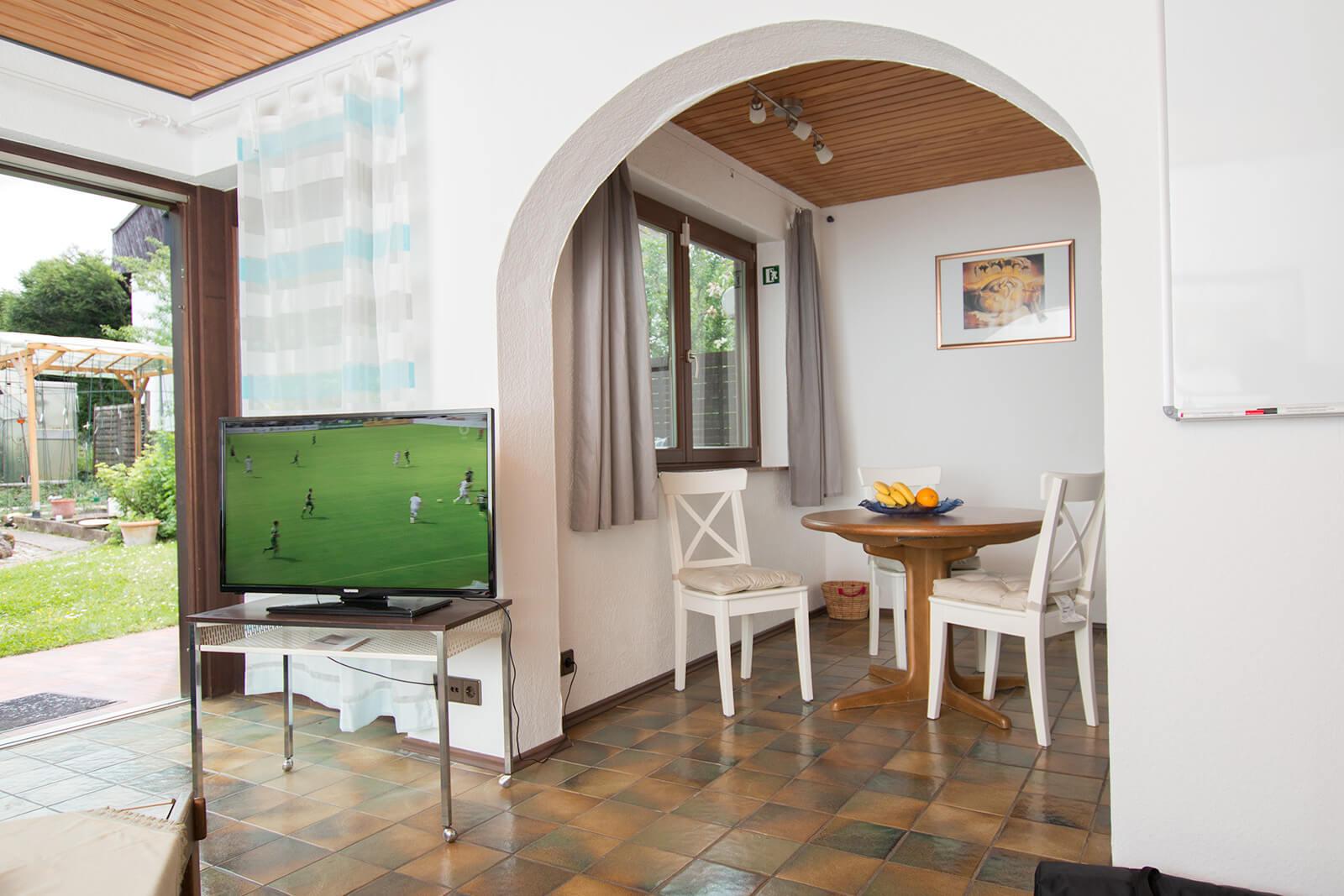 42 Zoll Flachbildschirm und Essecke mit Blick auf den Garten der Ferienwohnung