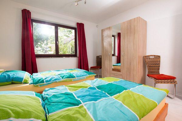Kleiderschrank und Stühle. Das Fenster kann neben den Vorhängen mit einem Rolladen vollständig abgedunkelt werden.